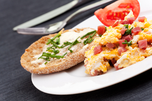 Creamy scrambled eggs with ham, tomatoes and roasted peppers