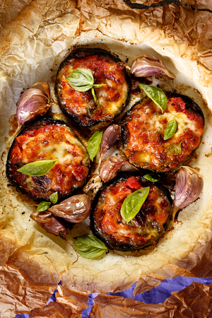 Garlic, tomato and melted cheese topped aubergines